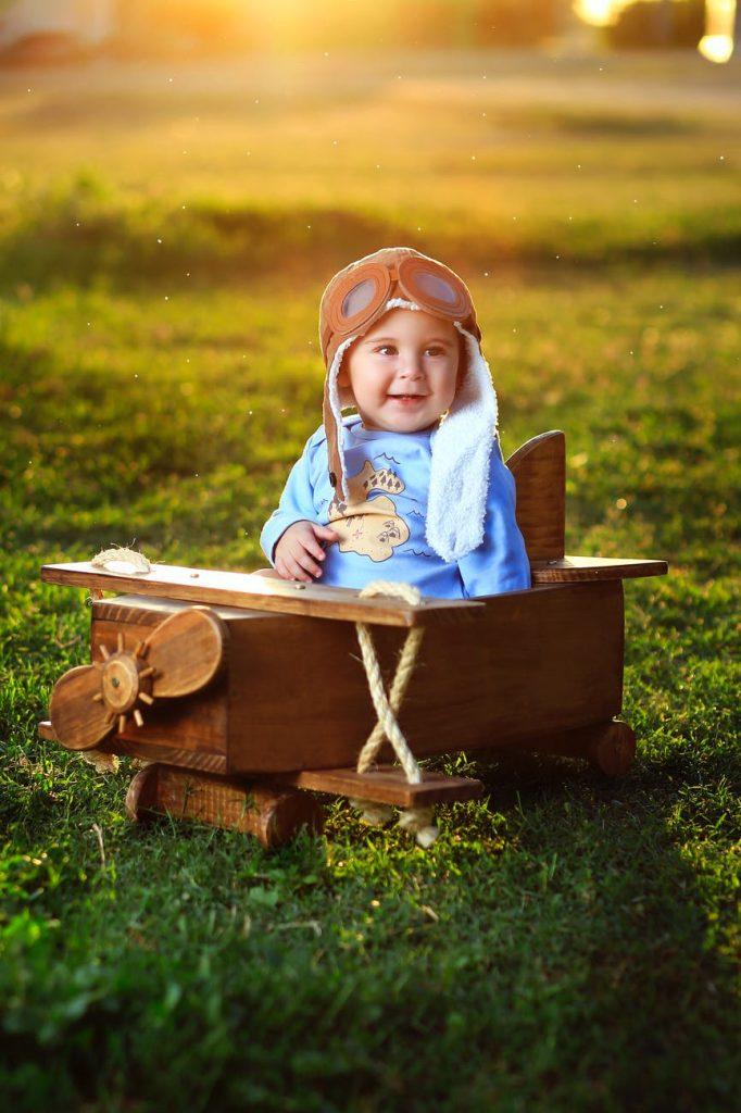 Niño feliz montado en un avión de juguete